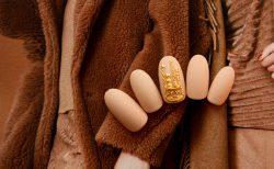 指先にゴールドのアクセサリー。秋冬にマットなジェルネイル。